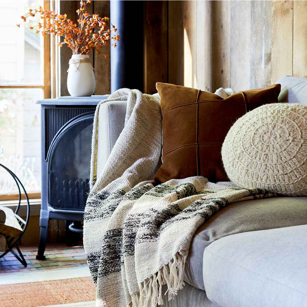 Cozy fall vignette with sripe throw, faux suede pillow and round hand crochet pillow - Target.