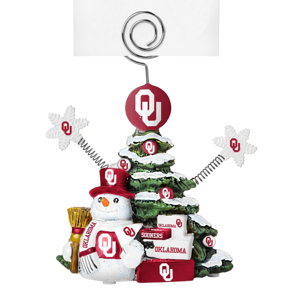 Oklahoma Sooners Tree Photo Holder Beautifully detailed cold cast porcelain tree with snowman and presents. Decorated with colofrul team graphics, this table sop holder is great for holding photos, notes to santa or place cards. Stands 5 tall Color: Oklahoma Sooners. Age Group: Adult.