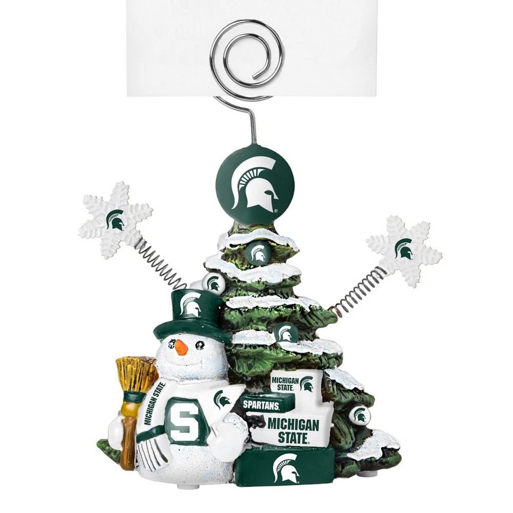 Michigan State Spartans Tree Photo Holder Beautifully detailed cold cast porcelain tree with snowman and presents. Decorated with colofrul team graphics, this table sop holder is great for holding photos, notes to santa or place cards. Stands 5 tall Color: Michigan State Spartans. Age Group: Adult.