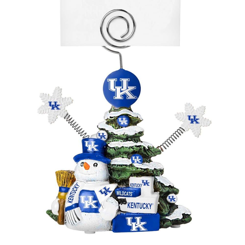 Kentucky Wildcats Tree Photo Holder Beautifully detailed cold cast porcelain tree with snowman and presents. Decorated with colofrul team graphics, this table sop holder is great for holding photos, notes to santa or place cards. Stands 5 tall Color: Kentucky Wildcats. Age Group: Adult.