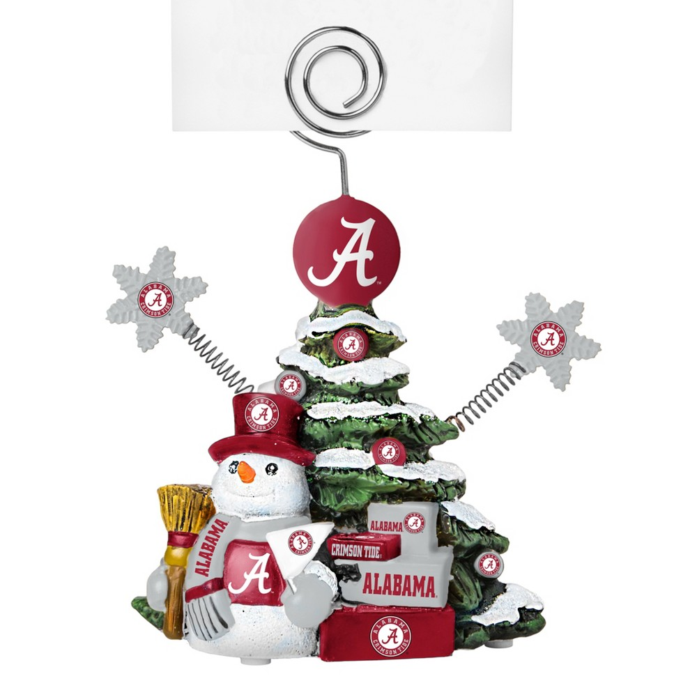 Alabama Crimson Tide Tree Photo Holder Beautifully detailed cold cast porcelain tree with snowman and presents. Decorated with colofrul team graphics, this table sop holder is great for holding photos, notes to santa or place cards. Stands 5 tall Color: Alabama Crimson Tide. Age Group: Adult.