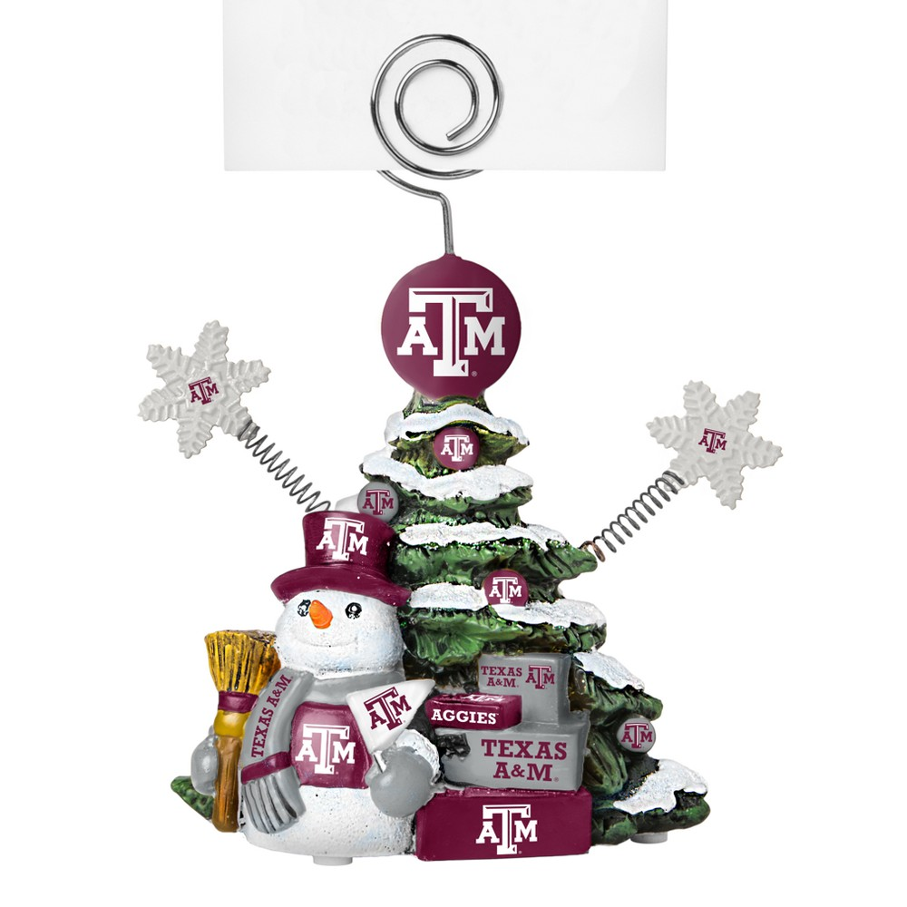 Texas A&m Aggies Tree Photo Holder Beautifully detailed cold cast porcelain tree with snowman and presents. Decorated with colofrul team graphics, this table sop holder is great for holding photos, notes to santa or place cards. Stands 5 tall Color: Texas A&m Aggies. Age Group: Adult.