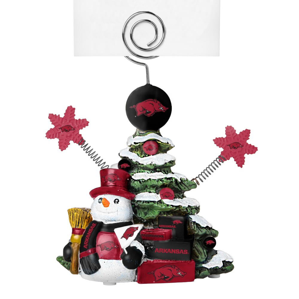 Arkansas Razorbacks Tree Photo Holder Beautifully detailed cold cast porcelain tree with snowman and presents. Decorated with colofrul team graphics, this table sop holder is great for holding photos, notes to santa or place cards. Stands 5 tall Color: Arkansas Razorbacks. Age Group: Adult.