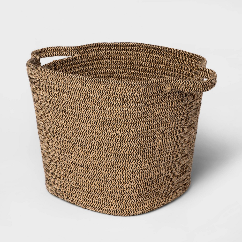 The Black and Natural Jute Rope Basket from Threshold? brings a stylish and functional update to your living space. Made from a durable cotton and jute material, this decorative basket features a natural woven pattern that brings traditional charm to your decor. Featuring an open-top design, it provides an effective solution to stow away toys, books or other household essentials to keep your home clutter-free, while the two side handles make it easy to move from one room to the other.