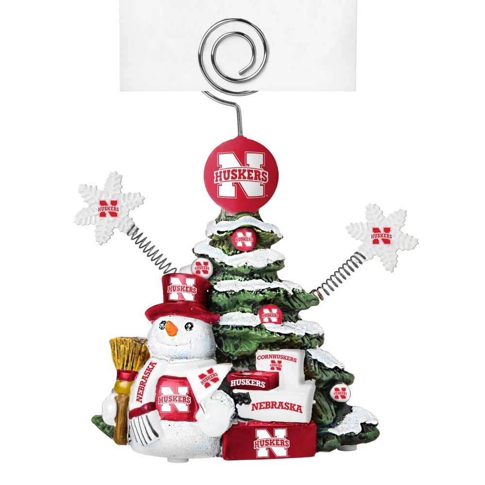 Nebraska Cornhuskers Tree Photo Holder Beautifully detailed cold cast porcelain tree with snowman and presents. Decorated with colofrul team graphics, this table sop holder is great for holding photos, notes to santa or place cards. Stands 5 tall Color: Nebraska Cornhuskers. Age Group: Adult.