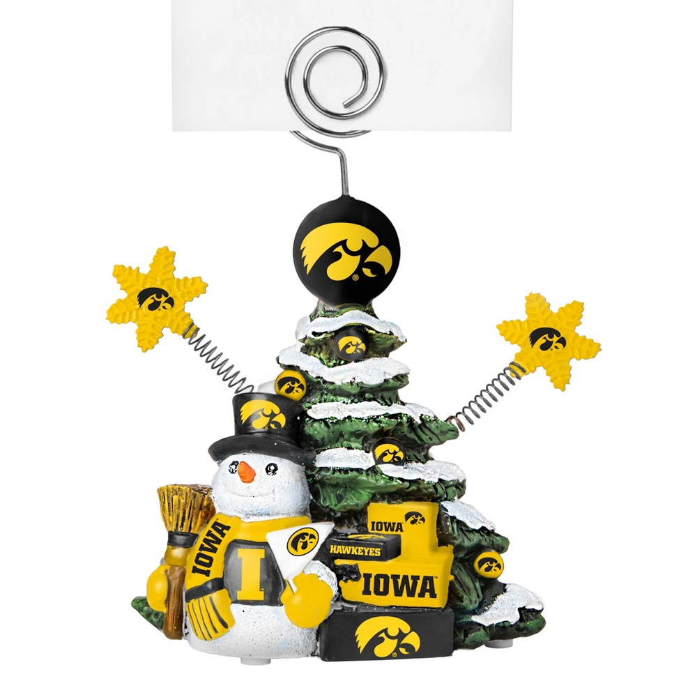 Iowa Hawkeyes Tree Photo Holder Beautifully detailed cold cast porcelain tree with snowman and presents. Decorated with colofrul team graphics, this table sop holder is great for holding photos, notes to santa or place cards. Stands 5 tall Color: Iowa Hawkeyes. Age Group: Adult.
