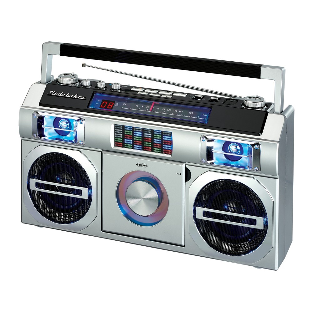 Studebaker 80's Retro Street Bluetooth Boombox with FM Radio, CD Player, Led EQ (SB2145) - Silver Reminiscent of the boomboxes of old, this portable CD Player with FM Analog Radio also includes Bluetooth connectivity for streaming music. The front loading CD player is CD-R/RW compatible. This unit comes with an auxiliary input jack and headphone jack. Other great features include built-in stereo speakers, rotary volume control, treble and bass adjustments and a convenient carrying handle. A multi-color Led Equalizer adds an exciting visual to this awesome looking unit. There is also a built-in AC transformer and built-in rechargeable battery. Color: Silver.