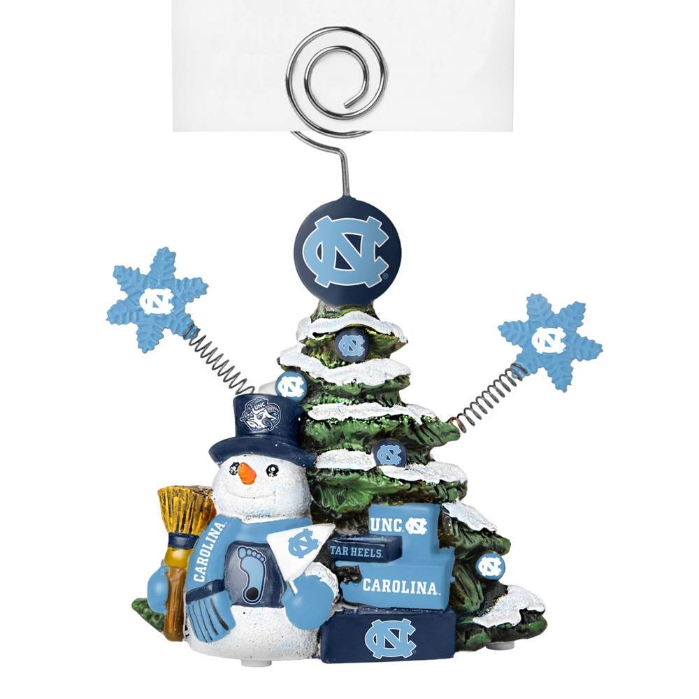 North Carolina Tar Heels Tree Photo Holder Beautifully detailed cold cast porcelain tree with snowman and presents. Decorated with colofrul team graphics, this table sop holder is great for holding photos, notes to santa or place cards. Stands 5 tall Color: North Carolina Tar Heels. Age Group: Adult.
