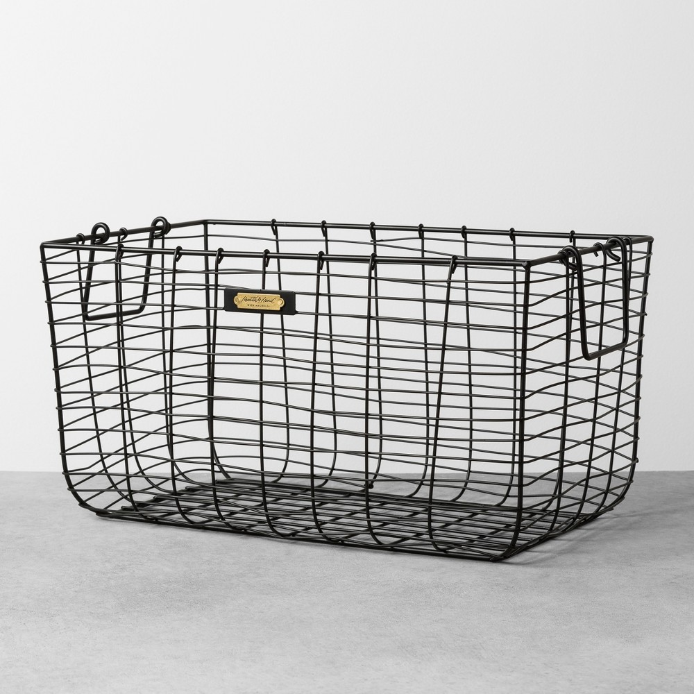 Create a decorative display on a bathroom counter, console table or on the lower shelf of a coffee table with the help of this Wire Storage Basket from Hearth and Hand? with Magnolia. Made with a sturdy metal frame with an airy wire design, this decorative storage basket is equipped with two handles for easy carrying and portability. With a small brass plate on the front with the Hearth and Hand logo, this metal wire storage basket is versatile piece for any room in your home. Celebrate the everyday with Hearth and Hand? created exclusively for Target in collaboration with Magnolia, a home and lifestyle brand by Chip and Joanna Gaines. Built upon our shared commitment to giving back to our communities, these pieces reveal the beauty of everyday moments shared with family and friends. Size: Large.