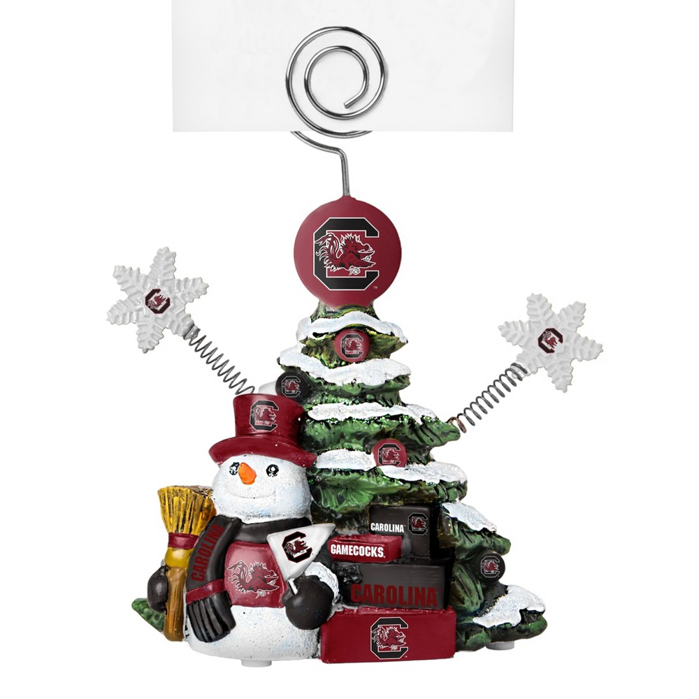 South Carolina Gamecocks Tree Photo Holder Beautifully detailed cold cast porcelain tree with snowman and presents. Decorated with colofrul team graphics, this table sop holder is great for holding photos, notes to santa or place cards. Stands 5 tall Color: South Carolina Gamecocks. Age Group: Adult.