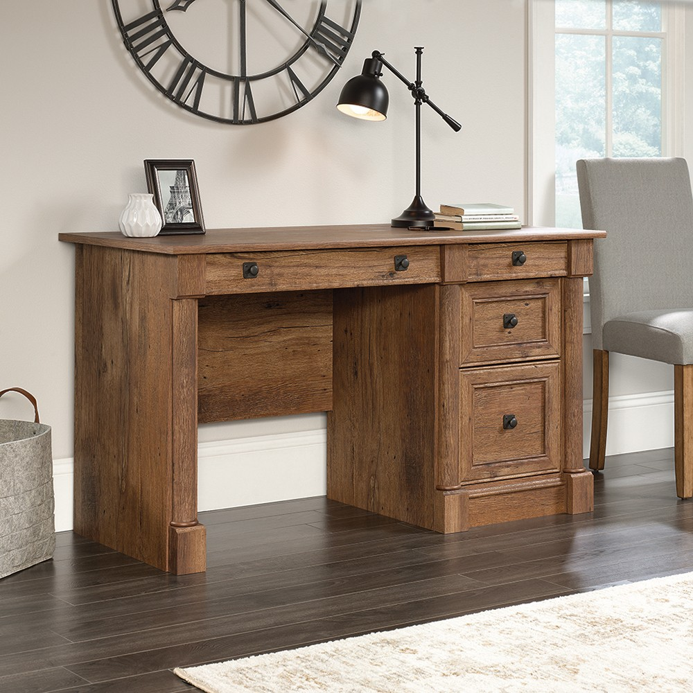 Whether you\\\'re in the office or at home, work in style with this desk from the Palladia collection. Its spacious work surface provides you with room for all your office essentials. It features a large slide-out drawer/shelf for a keyboard and mouse, along with two drawers that open and close on smooth metal runners. The lower drawer has full extension slides to hold letter-size hanging files to help keep you organized. Finished in a classy Vintage Oak, this desk will impress.