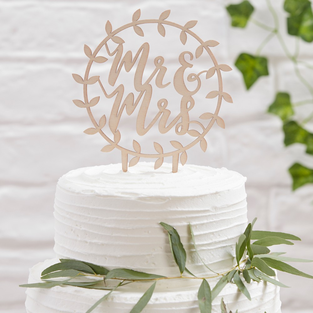 Ginger Ray Wooden Mr. And Mrs. Script Cake Topper Beautiful Botanics, Wood Make your wedding cake even more special by adding this gorgeous 'Mr and Mrs Wooden Cake Topper. The gorgeous scripted font will suit all wedding themes! This unique cake topper will look stunning on any wedding cake, the wooden topper will add instant chic to your wonderful wedding. Add a beautiful botanic feel to your cake with the stunning scripted vine design. Cake topper measures: 13.5cm (W) x 20cm (H) x 0.5cm (D). Color: Wood.