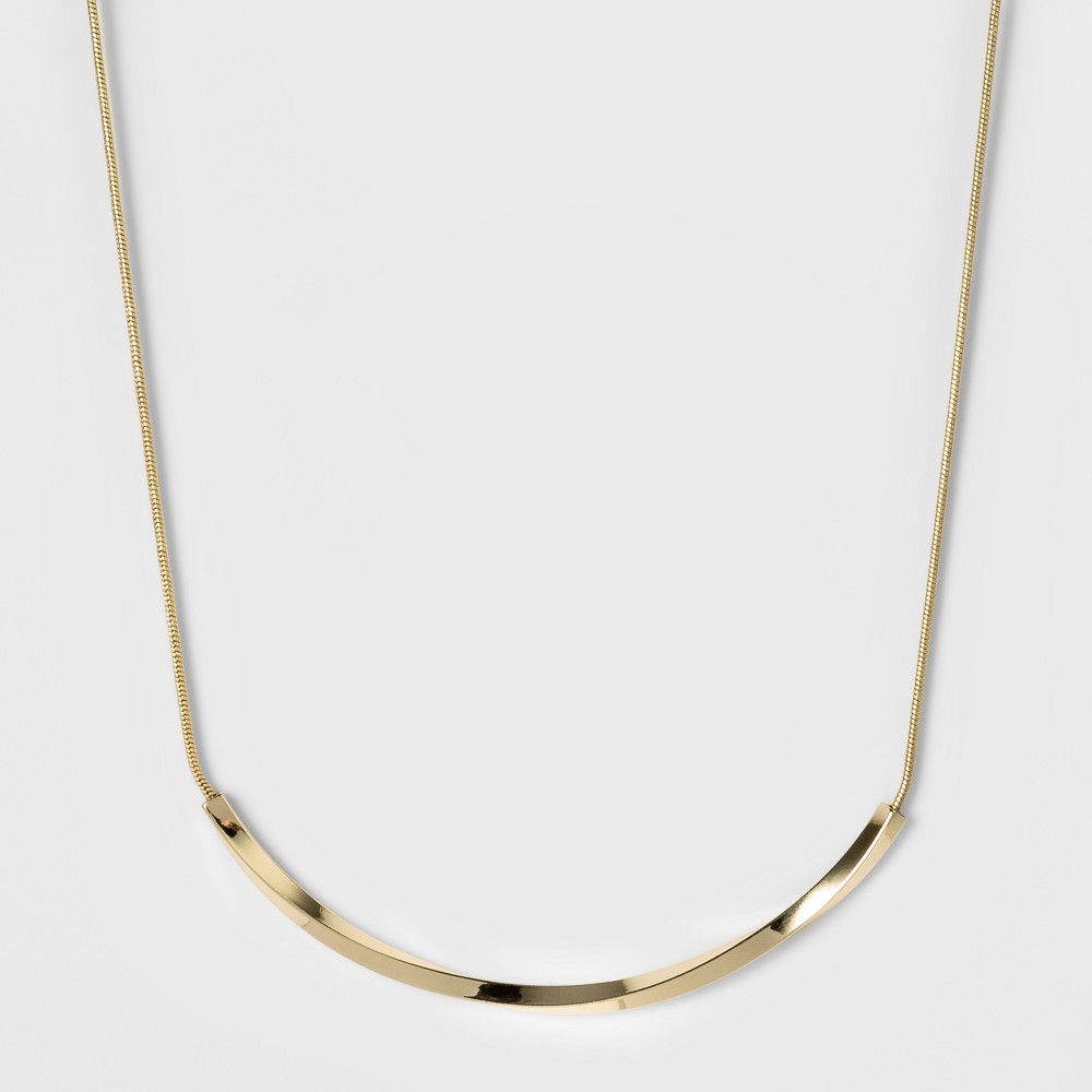 Women's Fashion Chain Necklace - A New Day Bright Gold Add a subtle shining accessory to your look with this Fashion Chain Necklace from A New Day. A simple snake chain is finished off with a sleek, twisting bar that gently curves at the bottom of the necklace. Pair this necklace with a variety of tops, dresses and necklines for a stunning look that can be dressed up or down. Color: Bright Gold. Gender: Female. Age Group: Adult.