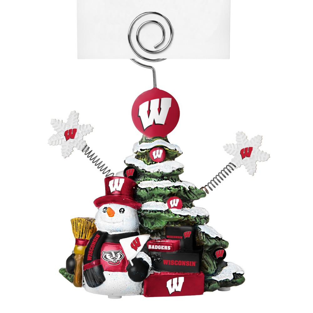 Wisconsin Badgers Tree Photo Holder Beautifully detailed cold cast porcelain tree with snowman and presents. Decorated with colofrul team graphics, this table sop holder is great for holding photos, notes to santa or place cards. Stands 5 tall Color: Wisconsin Badgers. Age Group: Adult.