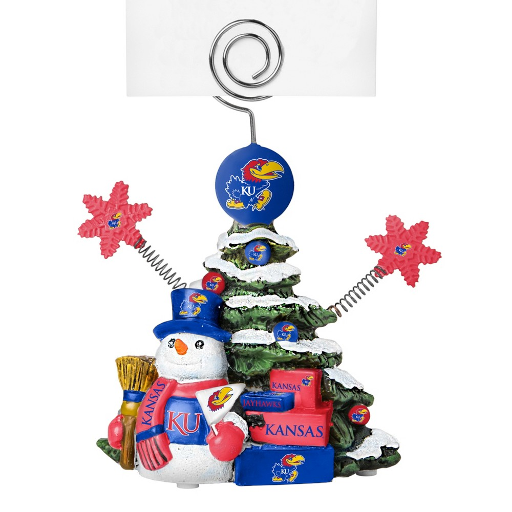 Kansas Jayhawks Tree Photo Holder Beautifully detailed cold cast porcelain tree with snowman and presents. Decorated with colofrul team graphics, this table sop holder is great for holding photos, notes to santa or place cards. Stands 5 tall Color: Kansas Jayhawks. Age Group: Adult.