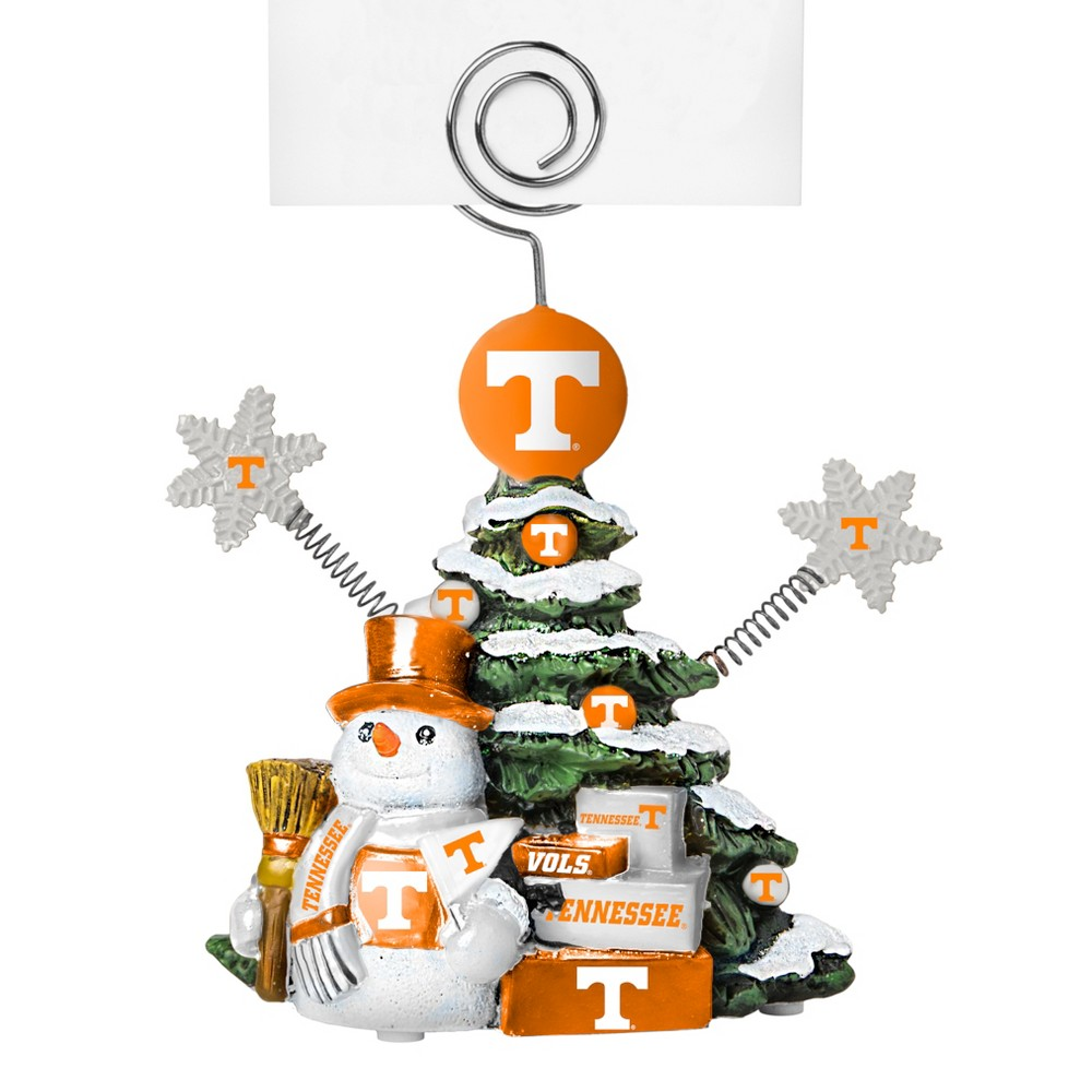 Tennessee Volunteers Tree Photo Holder Beautifully detailed cold cast porcelain tree with snowman and presents. Decorated with colofrul team graphics, this table sop holder is great for holding photos, notes to santa or place cards. Stands 5 tall Color: Tennessee Volunteers. Age Group: Adult.