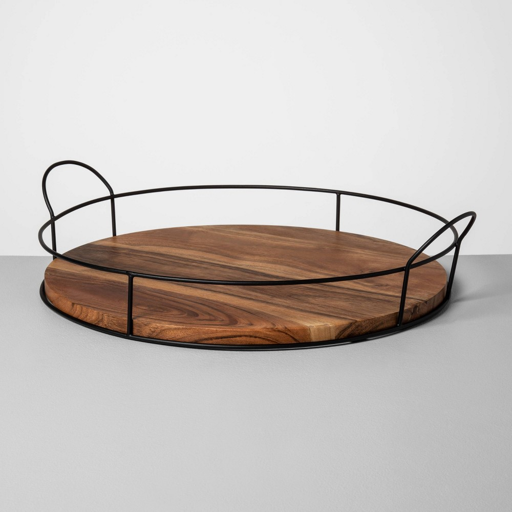 Whether you need a go-to spot to set your keys and wallet while at home or are looking for the perfect piece to display your favorite vase, the Wood and Metal Tray from Hearth and Hand? with Magnolia makes a great pick. This round decorative tray features a medium-hued wooden base, accented by a black metal wire rim. The simplistic style is easy to incorporate with a variety of decor to suit your aesthetic, and you\\\'ll appreciate how easy the attached handles make it to move throughout your space when you want to mix things up. Celebrate the everyday with Hearth and Hand? created exclusively for Target in collaboration with Magnolia, a home and lifestyle brand by Chip and Joanna Gaines. Built upon our shared commitment to giving back to our communities, these pieces reveal the beauty of everyday moments shared with family and friends.