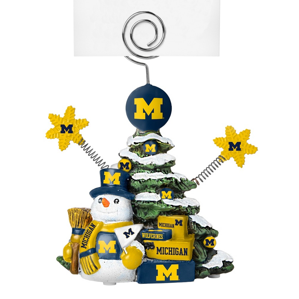 Michigan Wolverines Tree Photo Holder Beautifully detailed cold cast porcelain tree with snowman and presents. Decorated with colofrul team graphics, this table sop holder is great for holding photos, notes to santa or place cards. Stands 5 tall Color: Michigan Wolverines. Age Group: Adult.