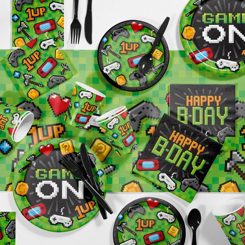 Video Game Birthday Party Kit Each Video Game Party Birthday Party Supplies Kit contains: 8 Video Game Party Paper Plates (9 ), 8 Video Game Party Dessert Plates (7 ), 16 Video Game Party Birthday Napkins (6.5 ), 16 Video Game Party Beverage Napkins (5 ), 1 Video Game Party Plastic Tablecloth (54  x 102 ), 8 Video Game Party Cups (9oz), and 8 Black Forks, Spoons, and Knives. Score big when you throw the birthday kiddo a party with this kit! Party supplies feature retro video game pixel graphics and a green and black color palette. This kit conveniently contains everything you need to serve your party foods. Coordinate the pieces in this kit with our other video game party supplies. Color: Multi-Colored. Gender: Unisex. Pattern: Letters.