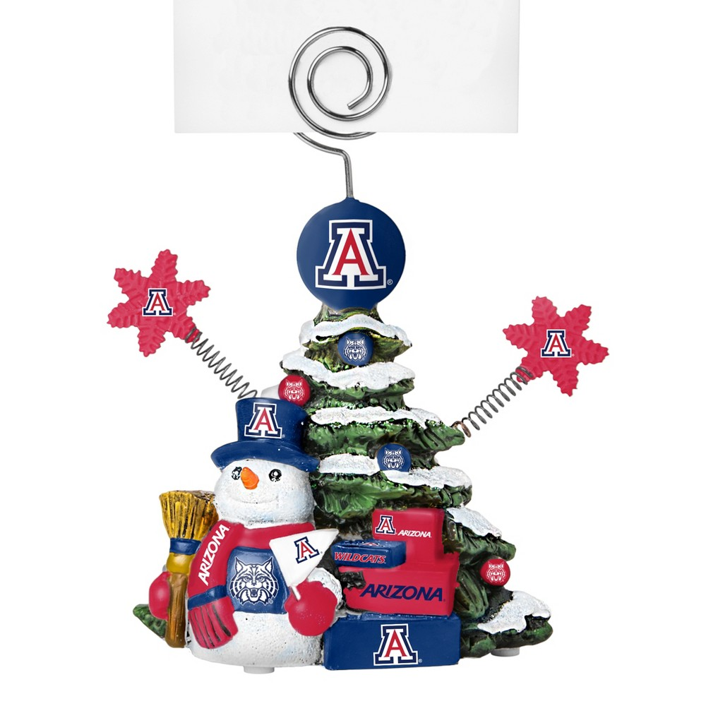 Arizona Wildcats Tree Photo Holder Beautifully detailed cold cast porcelain tree with snowman and presents. Decorated with colofrul team graphics, this table sop holder is great for holding photos, notes to santa or place cards. Stands 5 tall Color: Arizona Wildcats. Age Group: Adult.