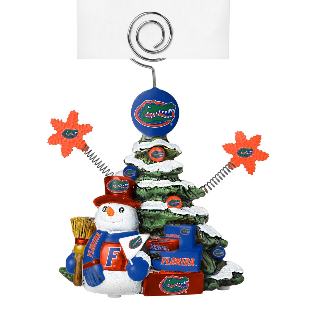Florida Gators Tree Photo Holder Beautifully detailed cold cast porcelain tree with snowman and presents. Decorated with colofrul team graphics, this table sop holder is great for holding photos, notes to santa or place cards. Stands 5 tall Color: Florida Gators. Age Group: Adult.