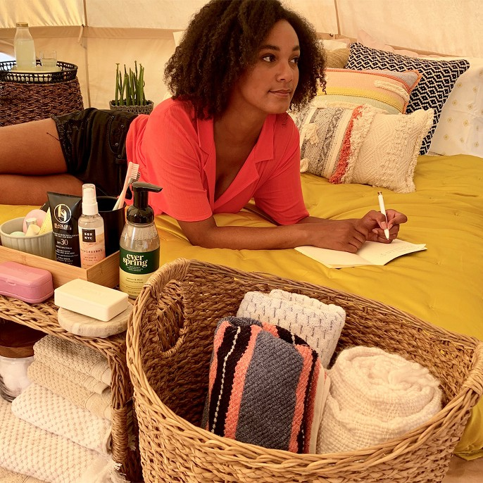 Photo of Olivia inside her tent journaling and relaxing on her queen sized air mattress complete with a plush yellow velvet comforter and cozy throw pillows.