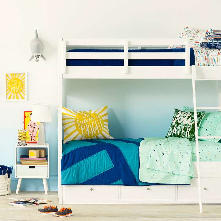 Twin Bunk Beds In A Kids Room Propped With Bedding And Decor From The Beachy
