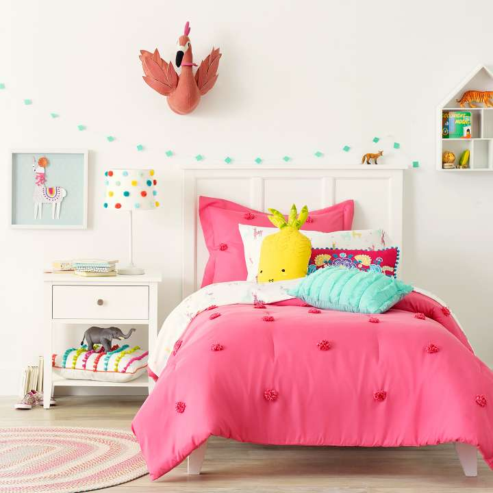 A Twin Bed In A Kids Room Full Of Bright Colors And Decor With Pom